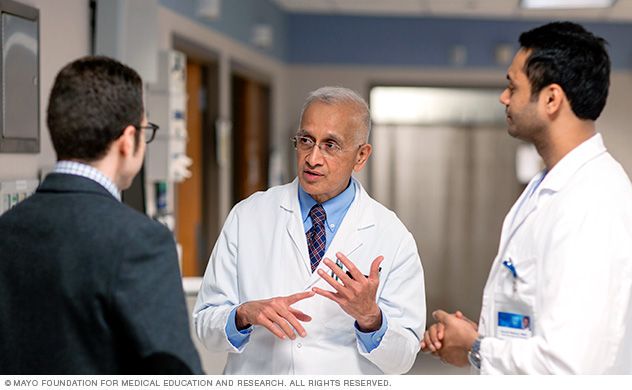 Photo of transplant hepatologist Patrick S. Kamath, M.D., discussing a case with fellows