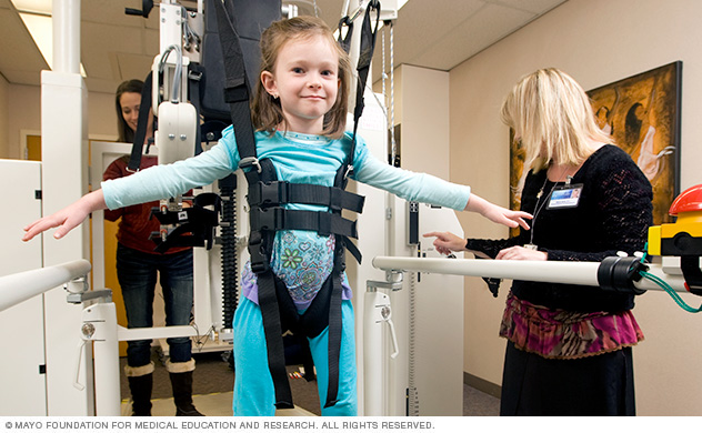Mayo Clinic physical therapist helping a child walk