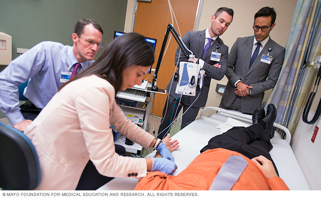 Mayo Clinic faculty member and residents examining a patient