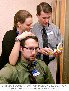 Two Mayo Clinic physical therapy orthopedic residents work with the program director when performing manual therapy to the cervical spine