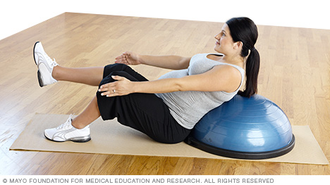 Pregnant woman practicing a v-sit supported by a balance trainer