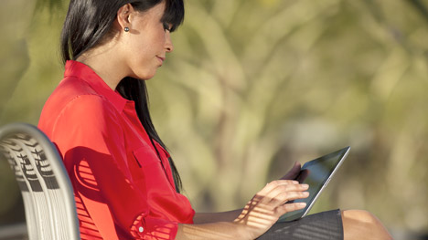Photo of a woman reading on a tablet
