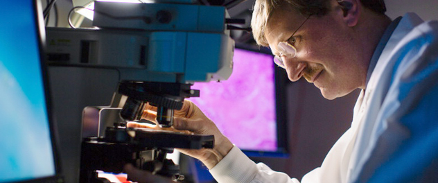 Image showing a researcher using a microscope to conduct breast cancer research
