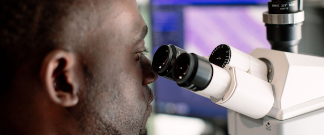 Research fellow using a microscope.